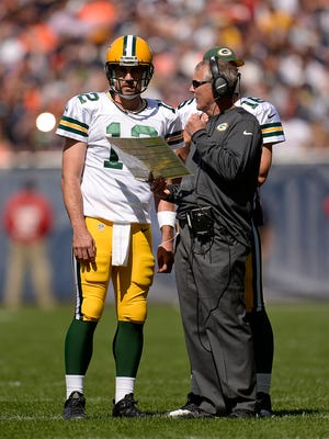 Green Bay Packers quarterback Aaron Rodgers talks with associate head coach Tom Clements during the third quarter against the Chicago Bears at Soldier Field in Chicago.
