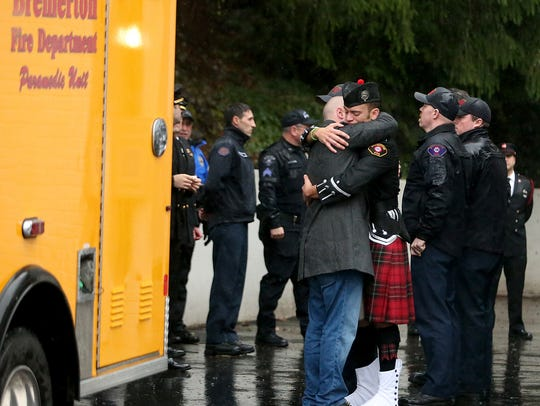 Former Bremerton firefighter Cory Chambers, left, embraces