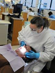 In this Dec. 4, 2009 photo, dental hygienist Jodi Hager