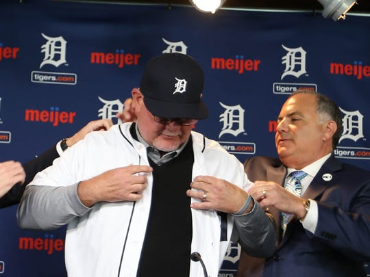 Al Avila, right, helps Ron Gardenhire get into a Tiger uniform when Ron was introduced as the new manager of the ball club on Friday, October 20, 2017 at Comerica Park in Detroit.