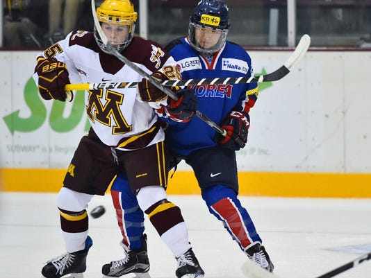 In this photo taken Sept. 24, 2017, South Korea's Marissa Brandt, right, defends against Minnesota forward Nicole Schammel in the first period of an exhibition hockey game in Minneapolis. Marissa, a native Korean who was adopted as an infant by parents in Minnesota, and her sister Hannah will both be playing in the upcoming Winter Olympics in women's hockey. Marissa for South Korea and Hannah for the U.S. (AP Photo/John Autey)