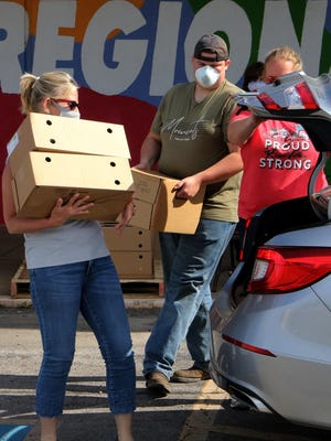 Lisa Woodard, from left, Philip Ramsey and Hattie Hamilton load boxes of fresh produce and four gallons of milk into a family car, Monday, June 1, 2020, during the weekly River Valley Regional Food Bank USDA commodities distribution day in front of the CSCDC parking lot, 1617 S. Zero.