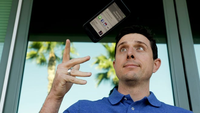 Aaron Norris poses for a picture with his smartphone near his office, in Riverside, Calif. Norris finds it's a struggle to let go of his electronic devices and the temptation to keep reading work email during his off hours.