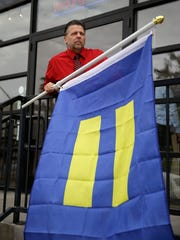 Logan Seven prepares to raise an equality flag at the