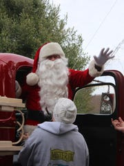 Santa arrives by antique fire truck at Mister Ed's Candy Emporium and Elephant Museum on Sunday, at the store's 40th annual event celebrating the big elf's arrival.
