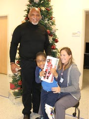 Cecil Fielder with Ayden Wallace, 5, of Paterson, and Kassandra Palmer, occupational therapist, PSE&G Children's Specialized Hospital.