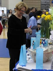Sandy DiFilippo of Sweet Water looks over the items up for sale at the silent auction.