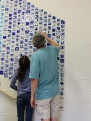 A student shows off her tile in the 880-tile mural