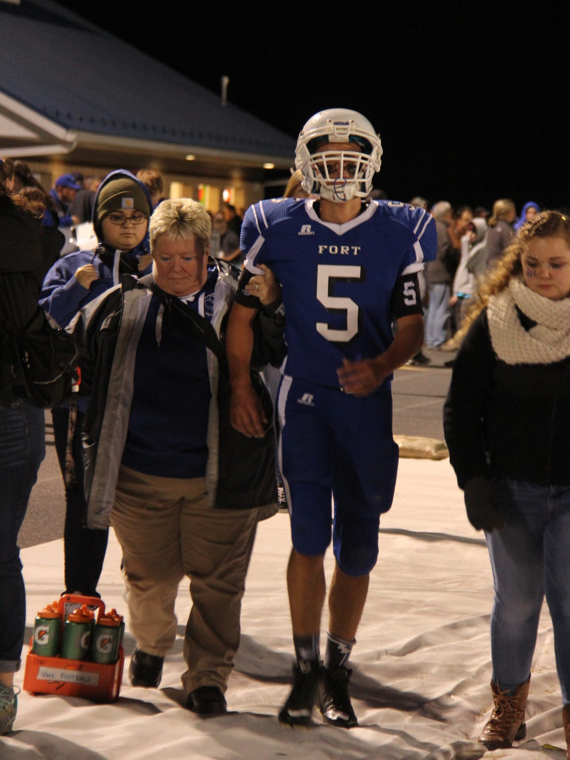 Becky Anhold helps a Fort Defiance football player off the field after injuring himself during a game.