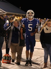Becky Anhold helps a Fort Defiance football player
