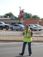 Crossing guard Crystal Broom works to make sure cars stop and students walk across the street safely.