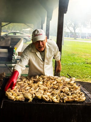 Frank Zgola, a member of the Trumansburg Rotary Club, prepares Robert Baker's famous Cornell Chicken, which has become an Election Day tradition.
