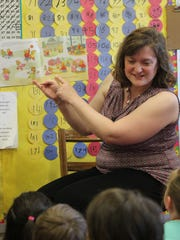 Londa Hart reads a graduation story to her students before they go to their kindergarten graduation ceremony.