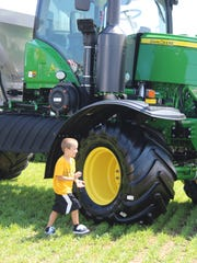 Cancer survivor Isaac Schneider checks out the John Deere machinery.