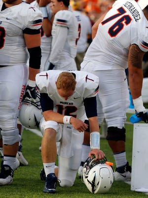 UTEP quarterback Ryan Metz kneels along the sidelines before the start of the game Saturday night.  The coaching staff yanked the junior quarterback in favor of freshman Mark Torrez in the 41-14 loss to NMSU.