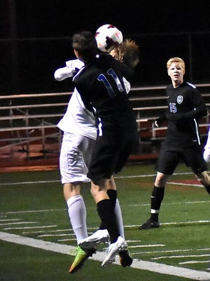 Sam Renggli (11) of Wyoming defends a header from Alter..