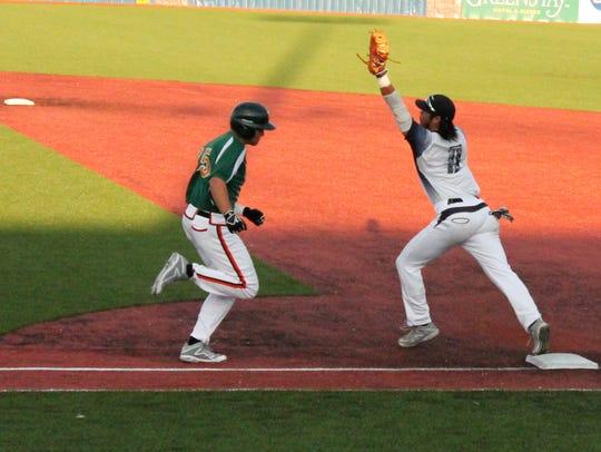 Cobras first baseman Masashi Sakatmoto holds up his