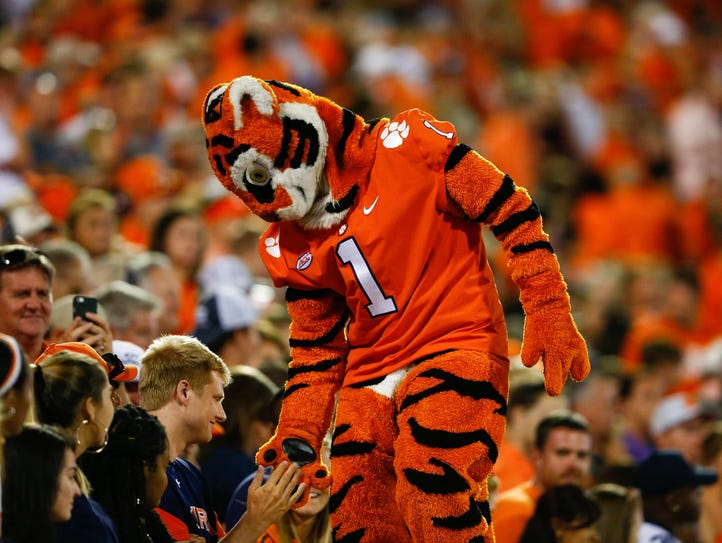 The Clemson Tigers mascot high fives fans during the