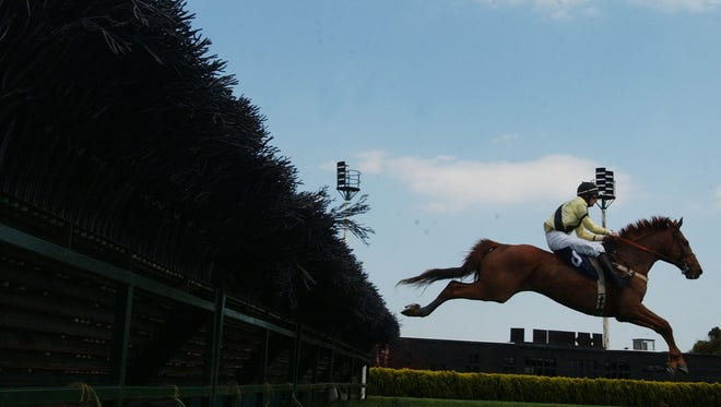 An unidentified riders makes a jump with his horse during a steeplechase race at the Atlantic City Race Course in Mays Landing, N.J. Wednesday, May 5, 2004.  The track is required by law to maintain some live races in order to provide simulcasting throughout the year. There are four live races schedule for this month.  Kenny's Crossing won the race (AP Photo/ Brian Branch-Price)