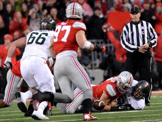 Spartan quarterback Damion Terry loses the ball as he is sacked Saturday  at Ohio Stadium in Columbus, Ohio in the first half of play against Ohio State.