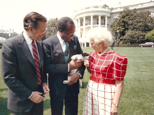 Benjamin Payton, President George HW Bush and Barbara Bush with a springer spaniel puppy at the White House during a Payton visit to Washington, DC.