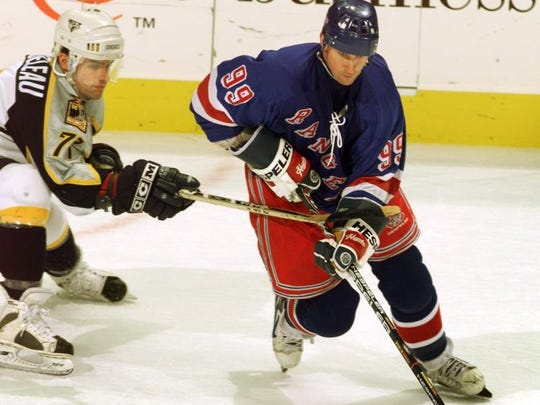 New York Rangers' Wayne Gretzky (99) moves the puck as Nashville Predators' Sebastien Bordeleau put a stick to try and hook him and steal the puck at the Nashville Arena Feb. 15, 1999.