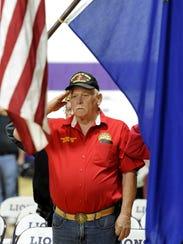 Marine veteran Robert Burgess salutes the flag.