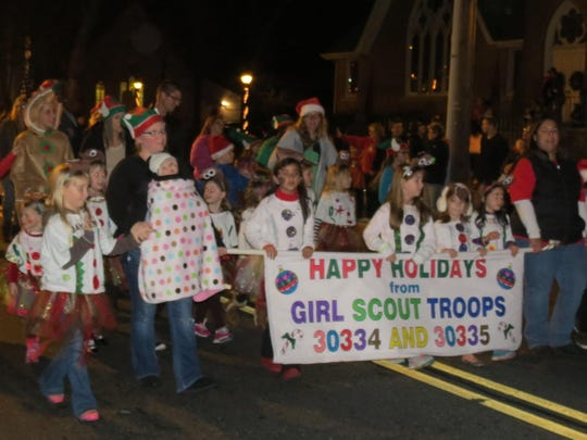 Girl Scouts from Troops 30334 and 30335 march down Bellvue Avenue during the Hammonton Christmas parade.