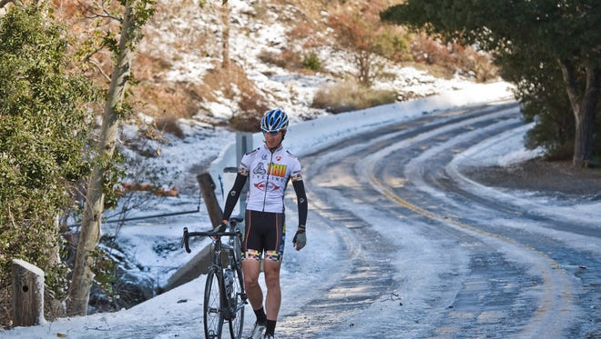 Cyclist John Janneck, 19, of Brea, Calif., walks his bicycle along a snow-and ice-covered road Wednesday, Dec. 31, 2014, in the Silverado area of Southern California after overnight snowfall.