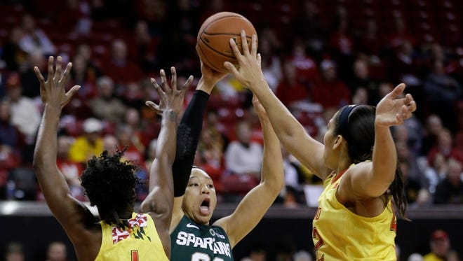 Maryland center Brionna Jones, right, blocks a pass attempt by Michigan State forward Aerial Powers as Powers is pressured by Jones and Laurin Mincy during the first half in College Park, Md.