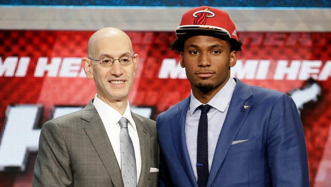 NBA commissioner Adam Silver shakes hands with basketball player Justise Winslow, right, after the Miami Heat selected him as the 10th pick in the first round of the 2015 NBA draft.