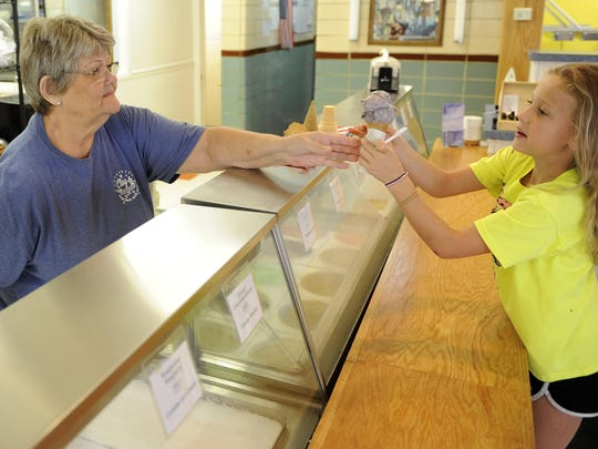 Sally Deckard, of Clay's Cafe and Catering, hands Bradlee Higgins a raspberry chip ice cream.