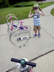 Calum Knull, 4, takes off his helmet and racks his scooter as he plays with mom Helen Knull, sister Grace, 7, and the family dog Marvin at Maguire Park on the River Trail in Lansing Friday, June 12.