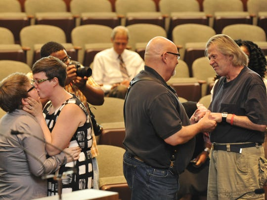 Same-sex couples, from left, Christina Wren, 31, and Katie Keyandwy, 28, of Redford have their first kiss of marriage while John Stevens, 63, and David Daily, 66, of Detroit savor the moment after legally taking their marriage vows in a group wedding ceremony in the auditorium of the Coleman A. Young Municipal Center.