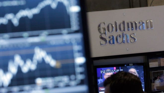 File photo taken in 2014 juxtaposes a video screen on the floor of the New York Stock Exchange with the Goldman Sachs booth.