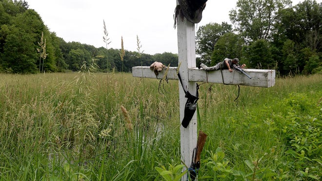 A cross stands near the site where the body of Ricky Holland was found in 2006. Items such as toy guns, a hat, an Army figure and a stuffed animal are tied to the cross and weathered from time. The site is near Dansville, at Williamston and Ewers roads in rural Ingham County.