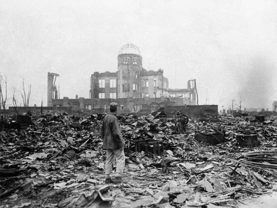 ** FILE - This Sept. 8, 1945 picture shows an allied correspondent standing in the rubble in front of the shell of a building that once was a movie theater in Hiroshima, Japan, a month after the first atomic bomb ever used in warfare was dropped by the U.S. on Monday, Aug. 6, 1945.