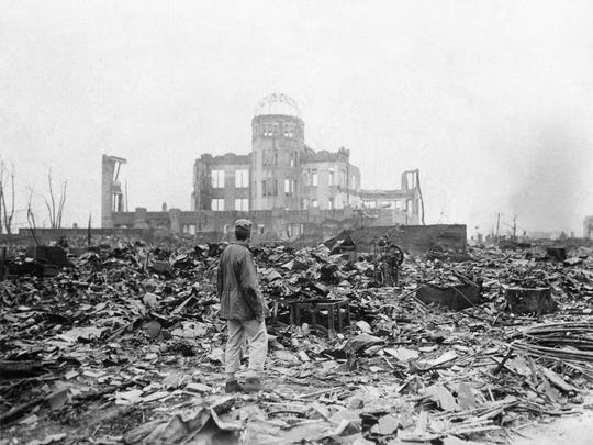FILE - In this Sept. 8, 1945 file photo, an allied correspondent stands in the rubble in front of the shell of a building that once was a movie theater in Hiroshima, Japan, a month after the first atomic bomb ever used in warfare was dropped by the U.S. on Aug. 6, 1945. They were the worst of enemies. Now they're the staunchest of allies. Japan and the U.S. have deep military and economic ties that have been a source of friction at times but largely bound them closely together in the post-World War II era.  (AP Photo/Stanley Troutman, File)