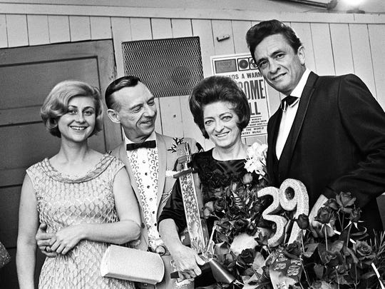 Mother Maybelle Carter, second from right, pose with Dixie Hall, left, Hank Snow, and Johnny Cash, right, backstage after she receives an award as the Grand Ole Opry celebrates their 41st birthday party at the Ryman Auditorium Oct. 21, 1966.