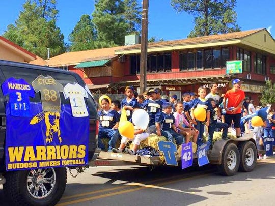 Members of the Warriors Little League football team roe in the parade.