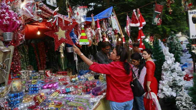 A woman shops for Christmas decorations at a market in Mumbai, India, Friday, Dec. 18. The World Bank estimates that less than 10 percent of the world's population lives in poverty.