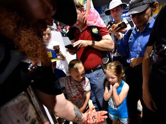 Red Hurd, a member of the Sweetwater Jaycees, holds a rattlesnake heart in the palm of his hand, showing it to the crowd gathered around the skinning pit at the World's Largest Rattlesnake Roundup in Sweetwater Saturday March 10, 2018. Thousands came out to attend the event, which this year marks 60 years.