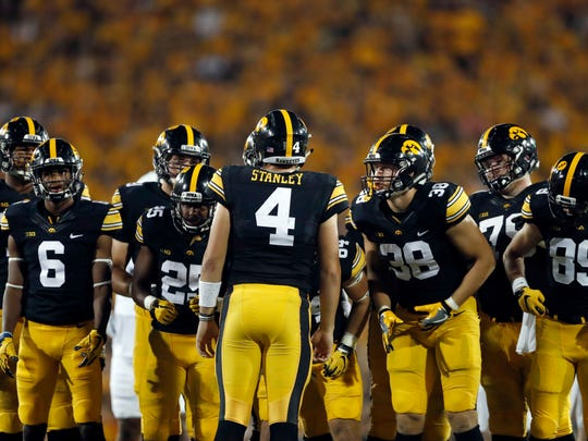FILE - In this Sept. 23, 2017, file photo, Iowa quarterback Nate Stanley (4) huddles with his team during the second half of an NCAA college football game against Penn State in Iowa City, Iowa. The strangest thing has happened to the Iowa Hawkeyes. They suddenly can't run the ball, and it's threatening their once-promising season.  (AP Photo/Jeff Roberson)