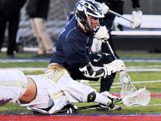South Lyon Unified's Drew Neller wins the face-off