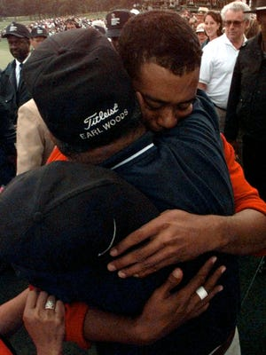 Tiger Woods hugs his father, Earl, after winning the 1997 Masters with a record-breaking 18-under-par for the tournament at the Augusta National Golf Club.