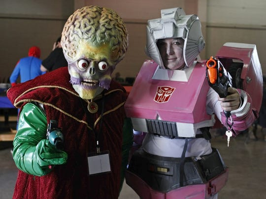 "Ryan Wells (left), as the Martian ambassador from ""Mars Attacks,"" and Allysha Butler, a Arcee from ""Transformers,"" pose for a photo at 2014 Cherry City Comic Con. Wells will return as a cosplay guest this year."