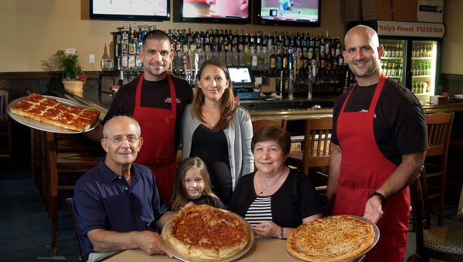The DiBella family is pictured at Italy's Finest Pizzeria in 2011. The restaurant recently closed, but Sal DiBella (standing, left) said it will re-open in a new location soon. Meanwhile, he and his brother have opened Woody's Sports Bar in Pace. Pictured are (l-r standing) Sal DiBella, Kiim DiBella and Joe DiBella. (Seated l-r) Pietro DiBella, Gianna DiBella, 4, and Lina DiBella.