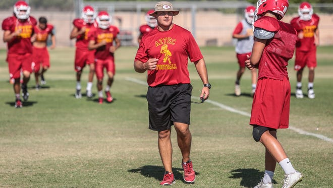 Palm Desert High School football head-coach Shane McComb works with his team at practice on Tuesday, August 9, 2016 in Palm Desert.