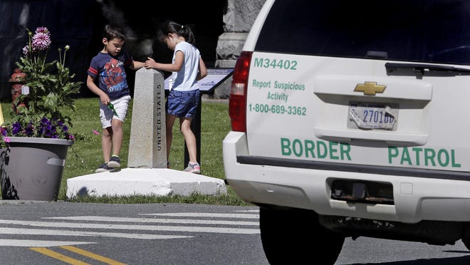 In this Wednesday, July 11, 2018 photo, two children, visiting the Haskell Library with their grandmother from Venezuela, play on the border pillar, as they circle back and forth between the United States and Canada under the watchful eye of a U.S. Border Patrol agent, seated in a vehicle, in Derby Line. The entrance to the library the family were visiting is in Vermont and while the boundary line with Canada goes right through the center of the building.