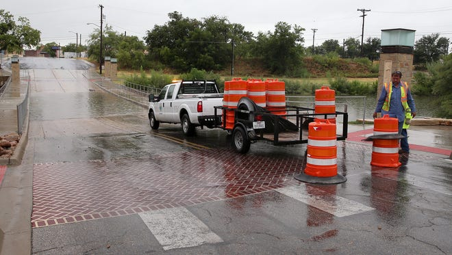 City workers set up blocks at the Irving Street bridge as water flows over the road into the Concho River on Aug. 9, 2016.